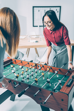 young attractive businesswomen playing table football in modern office Stock fotó