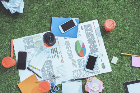 heap of business objects and office supplies laying on green grass carpet at office, business establishment