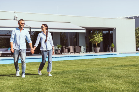smiling couple holding hands and walking on green lawn near swimming pool at country house