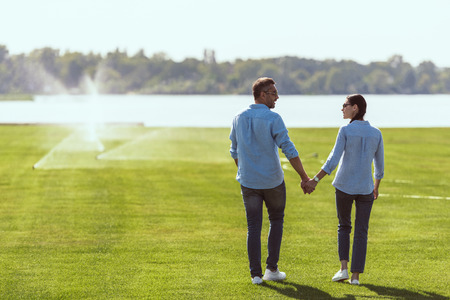 couple in sunglasses holding hands and looking at each other at lawn outdoors Stock Photo