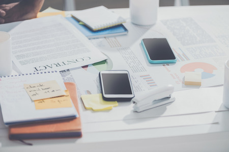 smartphones with contract and notebooks with stapler on table at modern office, business establishment