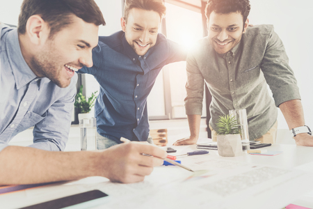 Three young businessmen leaning at table and working at project together, business teamwork concept Stock Photo