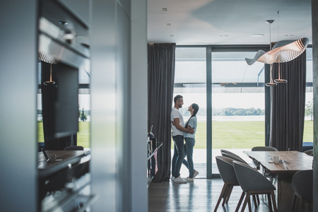 distant view of handsome adult man embracing attractive girlfriend at home Reklamní fotografie