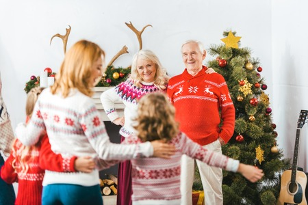 happy grandparents looking at daughter with grandkids at home during christmas 写真素材