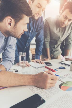 Trzech młodych biznesmenów opierając się przy stole i pracując nad projektem razem, koncepcja pracy zespołowej firmy