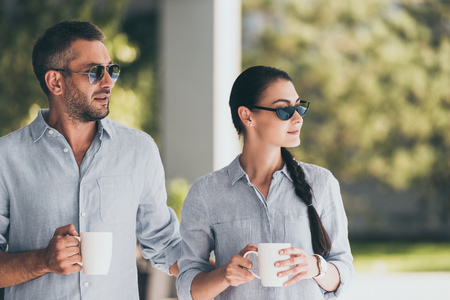 selective focus of couple in sunglasses with coffee cups outdoors