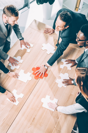 high angle view of multiracial businesspeople assembling puzzle on conference table Stok Fotoğraf