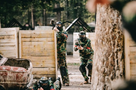 selective focus of paintball team in uniform and protective masks playing paintball with marker guns outdoors
