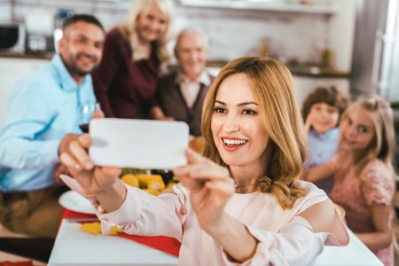 happy young woman taking selfie with her family during thanksgiving dinner Stock Photo