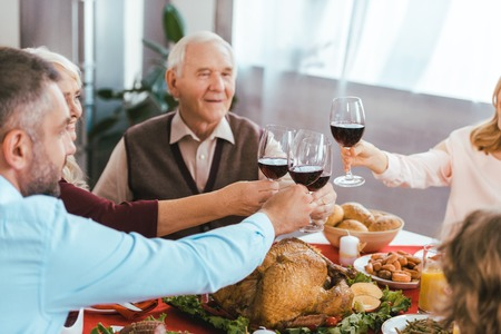 beautiful happy family clinking glasses of wine during thanksgiving dinner