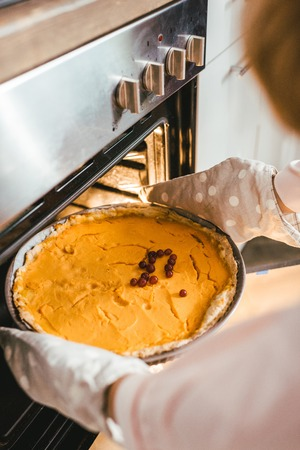 cropped shot fo woman taking out delicious pumpkin pie from oven