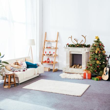 junge Frau, die auf der Couch im weihnachtlich dekorierten Wohnzimmer schläft