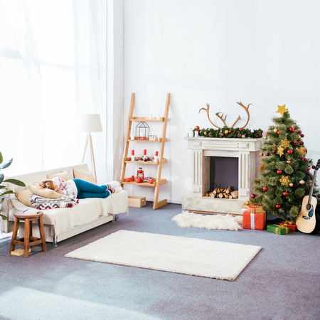 young woman sleeping on couch in christmas decorated living room Stock Photo