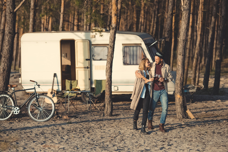 young happy couple with glasses of wine walking near campervan