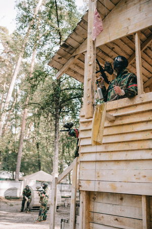 low angle view of paintball player on wooden tower removing flag from flagpole outdoors