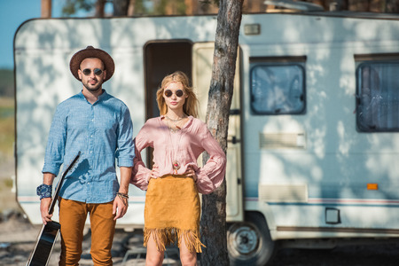 young hippie couple of campers posing near trailer Stock Photo