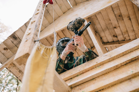 low angle view of paintball player in goggle mask and camouflage aiming by paintball gun on wooden tower outdoors Stockfoto