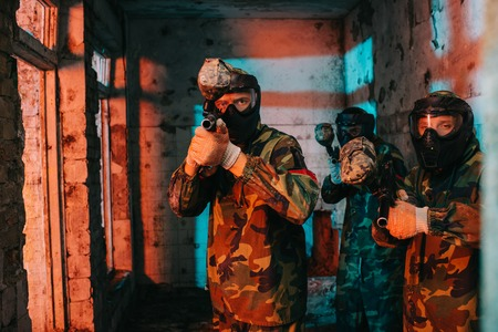paintball team in uniform and protective masks aiming by paintball guns in abandoned building Reklamní fotografie