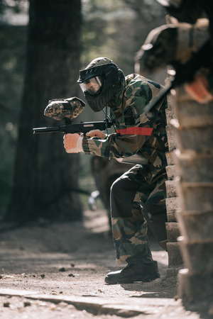 selective focus of male paintball player in goggle mask and camouflage aiming by paintball gun outdoors Stock fotó - 109145370
