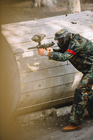 side view of focused paintball player in goggle mask and camouflage aiming by paintball gun outdoors Stock Photo