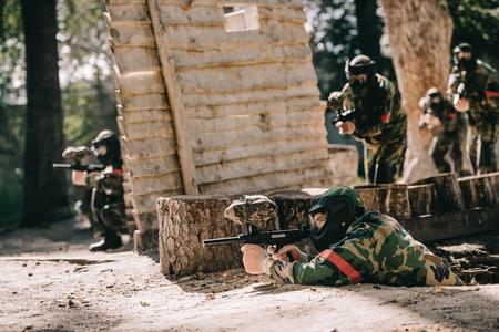 彼のチームが屋外の木製の壁の後ろに隠れている間、地面に横たわってマーカー銃で狙うペイントボールプレーヤー 写真素材 - 109145470