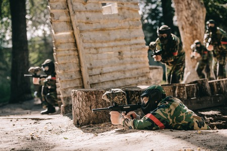 paintball player laying on ground and aiming by marker gun while his team hiding behind wooden wall outdoors Foto de archivo