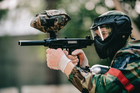 side view of male paintball player in goggle mask and camouflage aiming by paintball gun outdoors Stockfoto