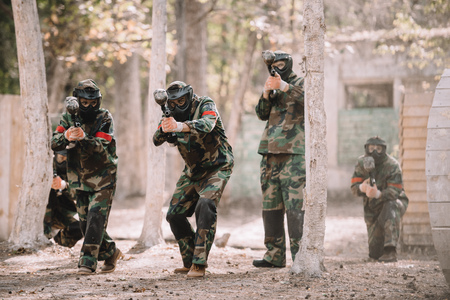 paintball team in uniform and protective masks running and aiming by paintball guns outdoors Banco de Imagens