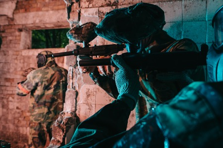 partial view of paintball team in uniform and protective masks playing paintball with marker guns in abandoned building