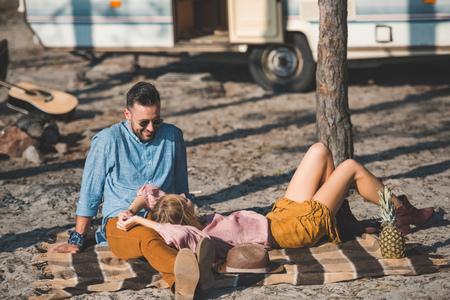 attractive couple lying on blanket near camper van