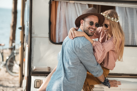 happy couple in sunglasses smiling and embracing while sitting on trailer Banco de Imagens