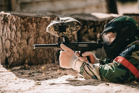 focused male paintball player in goggle mask and camouflage aiming by paintball gun outdoors