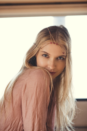beautiful blonde hippie girl in hair decoration looking at camera