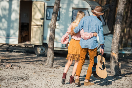 rear view of hippie couple hugging and walking with guitar near trailer