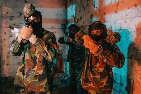 paintball team in uniform and protective masks aiming by paintball guns in abandoned building Banco de Imagens