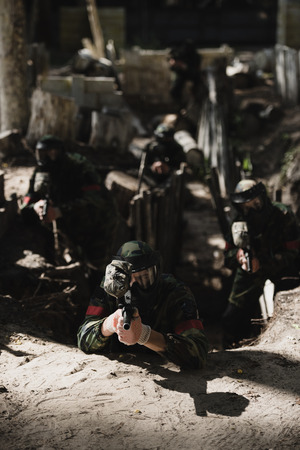 paintball team in camouflage and protective masks aiming by marker guns from ditch outdoors