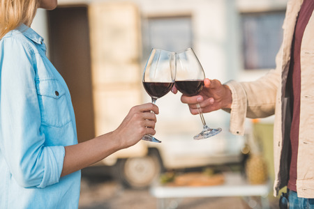 cropped view of couple clinking with glasses of red wine near campervan