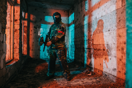 confident male paintball player in goggle mask and camouflage holding paintball gun in abandoned building