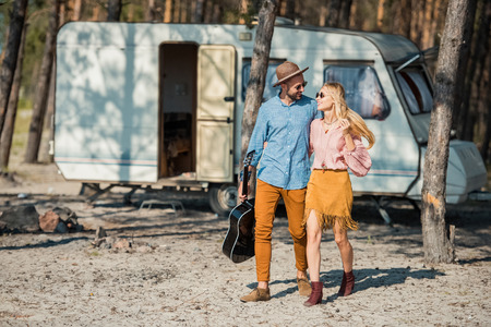 beautiful couple hugging and walking with acoustic guitar near campervan in forest