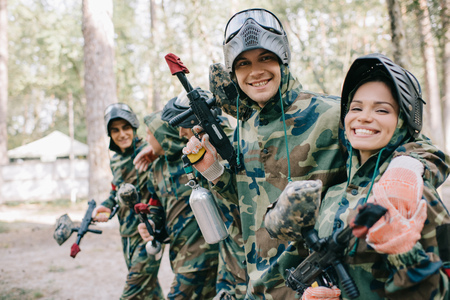 smiling young male paintballer embracing female teammate in camouflage with paintball gun outdoors 版權商用圖片
