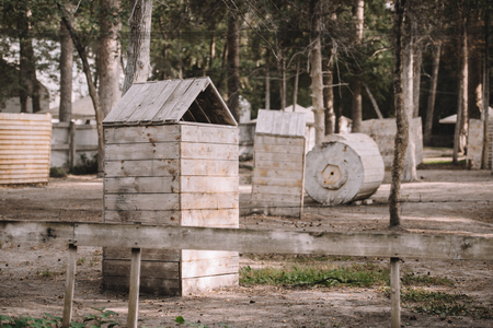 scenic view of paintball club with wooden constructions and trees outdoors Фото со стока