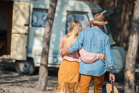 back view of hippie couple hugging and holding guitar near campervan Banco de Imagens