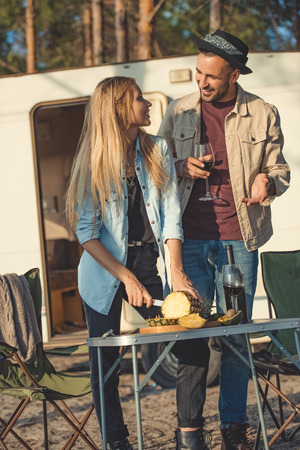 beautiful girl cutting pineapple and looking man with wine near campervan