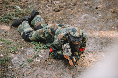 high angle view of male paintball player in goggle mask and camouflage crawling with paintball gun outdoors Banco de Imagens