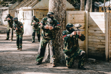 paintball players wearing camouflage and goggle masks shooting by markers guns near tree and their team on background outdoors Reklamní fotografie