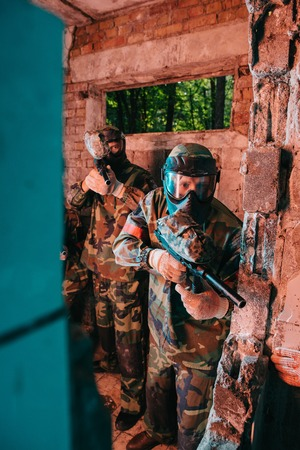 paintball team in uniform and protective masks playing standing with paintball guns in abandoned building Reklamní fotografie