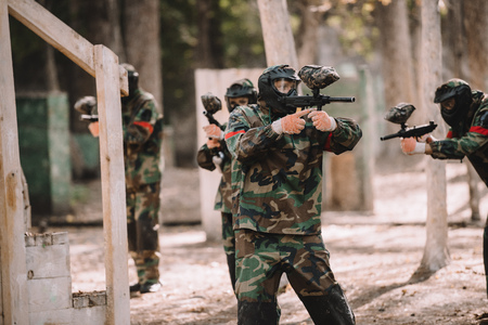 paintball team in uniform and protective masks shooting by paintball guns outdoors