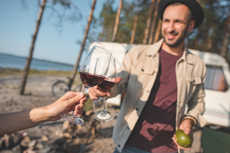 young man and woman clinking with glasses of wine walking near campervan Banco de Imagens