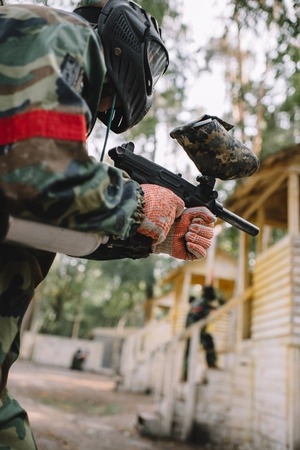 low angle view of male paintball player in goggle mask and camouflage aiming by paintball gun outdoors Stockfoto