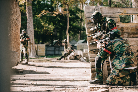 paintball players in camouflage and protective masks aiming with marker guns and hiding behind wooden wall outdoors Reklamní fotografie